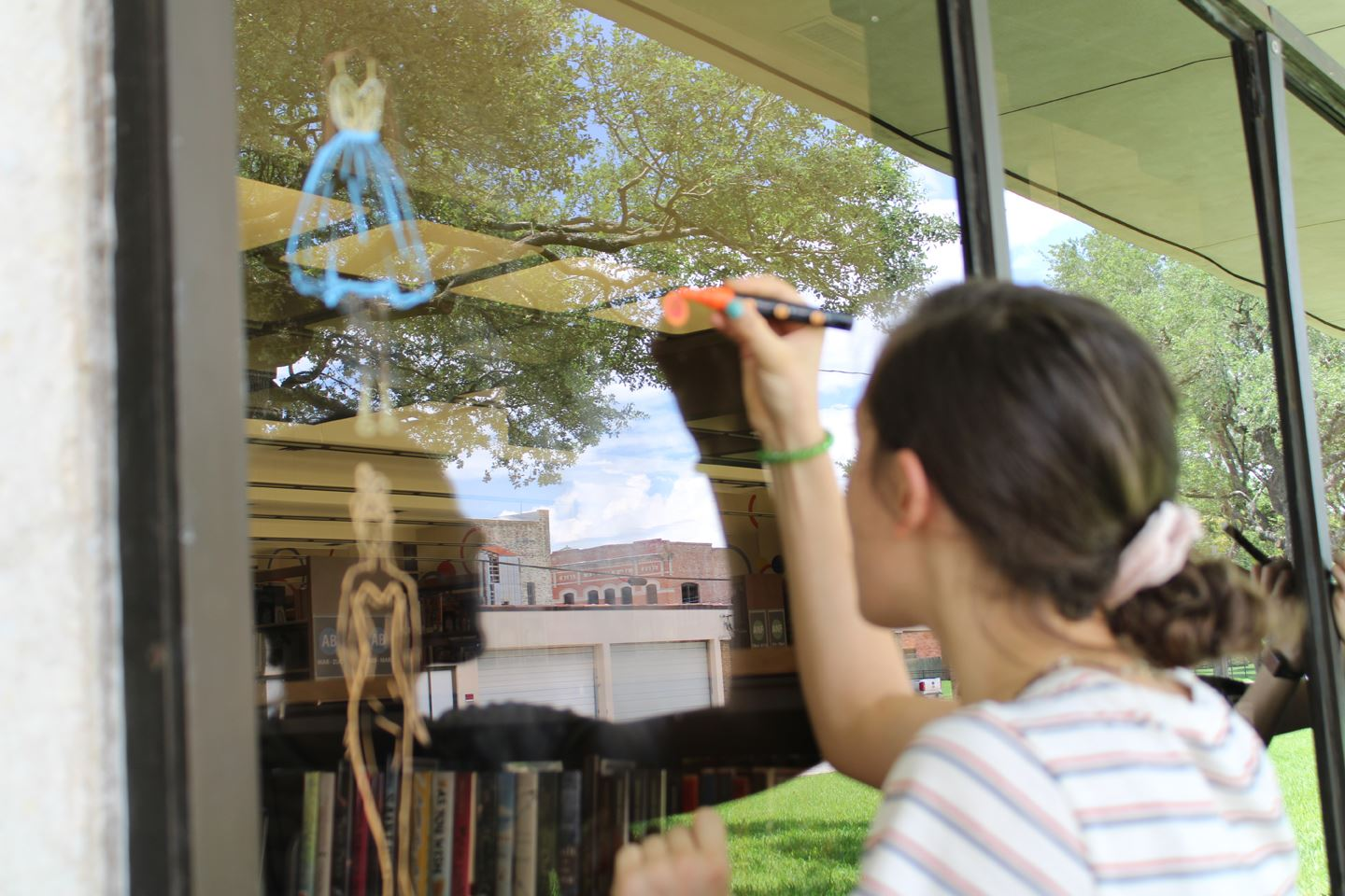 Girl decorates library window