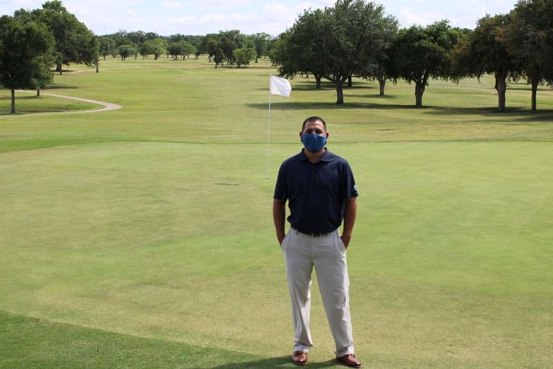 Man stands on golf course wearing facial covering