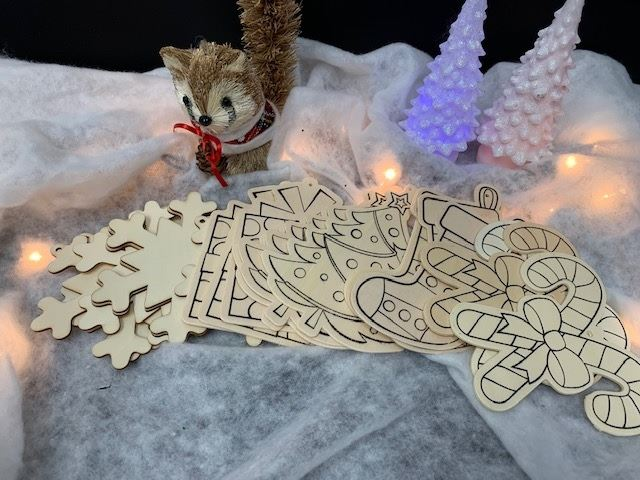Wooden ornaments with Christmas designs are displayed in a faux snowscape with Christmas lights.