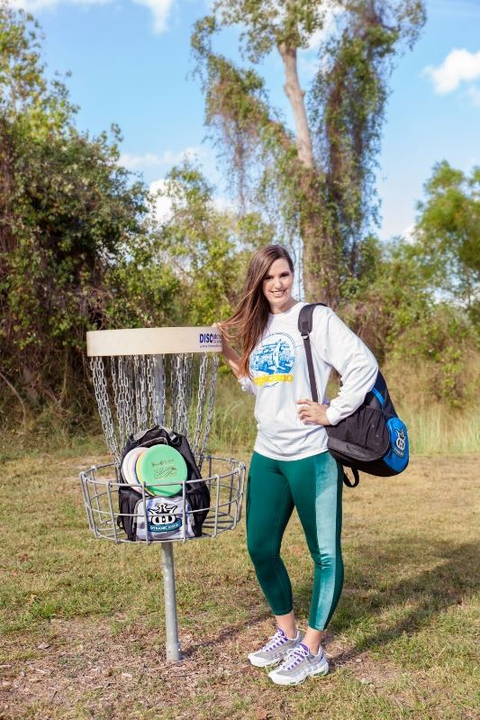 Smiling woman stands near a disc golf goal basket in Riverside Park that contains discs and a bag.