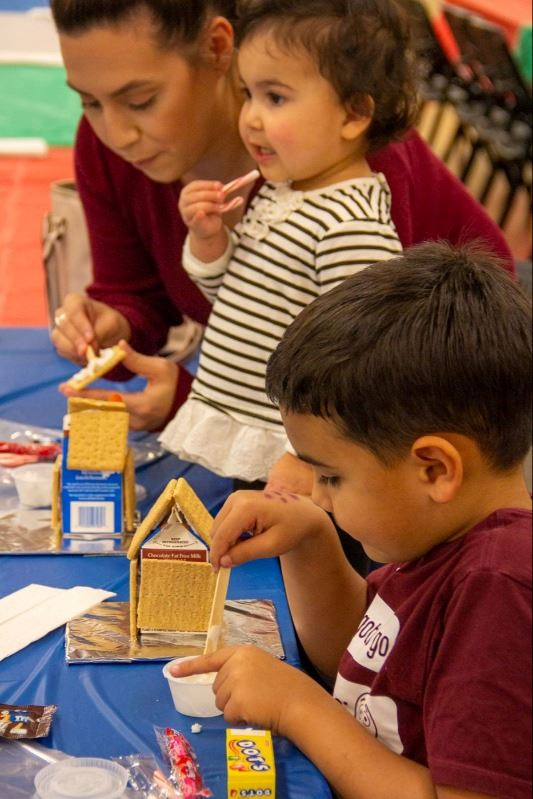 A woman and two children build gingerbread houses from graham crackers, milk cartons and candy.