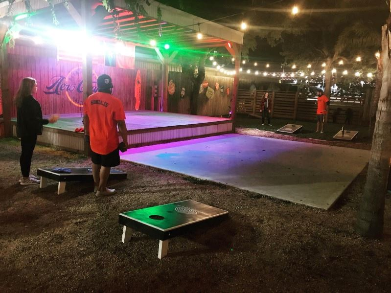 People play cornhole on an outdoor patio at night beneath string lights near Aero Crafters stage.