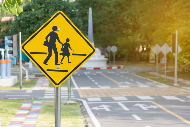 A crossing sign featuring an adult and child near a street marked with crosswalks and turn lanes.