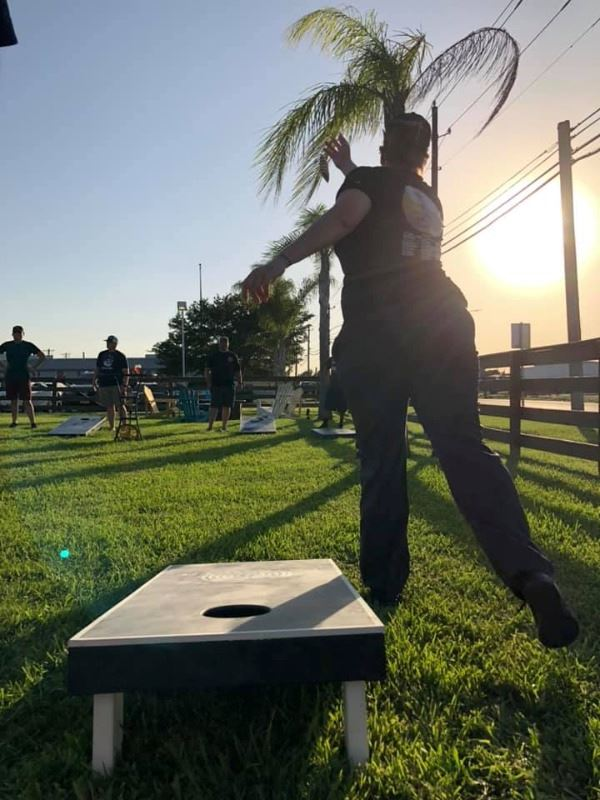 Woman is silhouetted throwing a cornhole bag during a game of cornhole outside in the evening.
