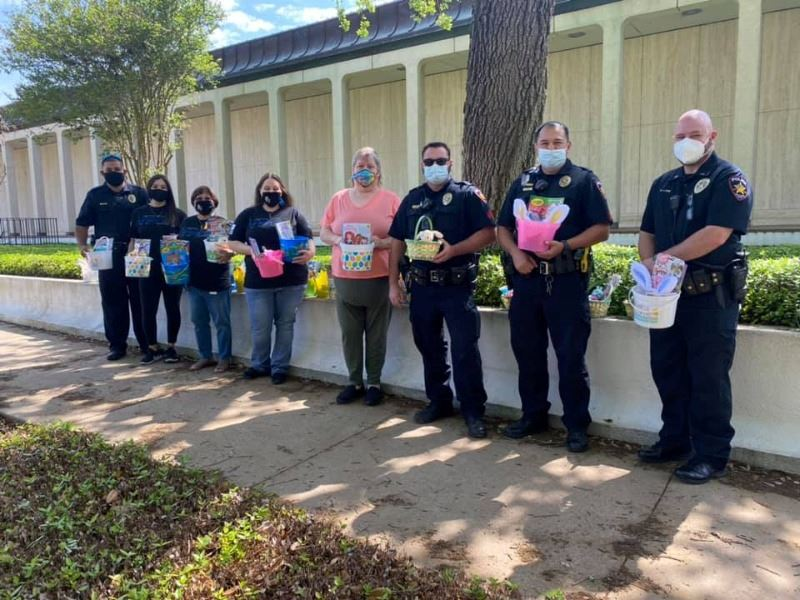 A group including uniformed police officers stands along an outdoor wall holding Easter baskets