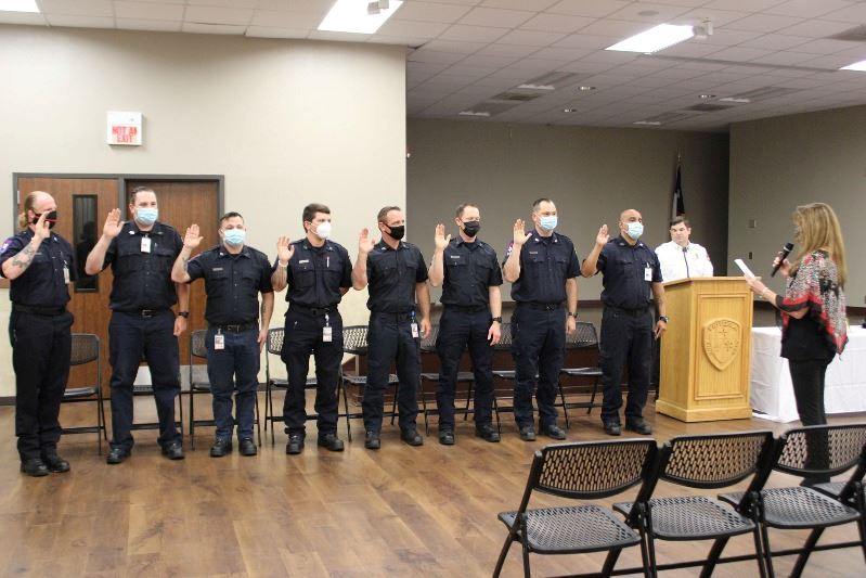 Five people in firefighter dress shirts raise their hands as they are sworn in by a woman