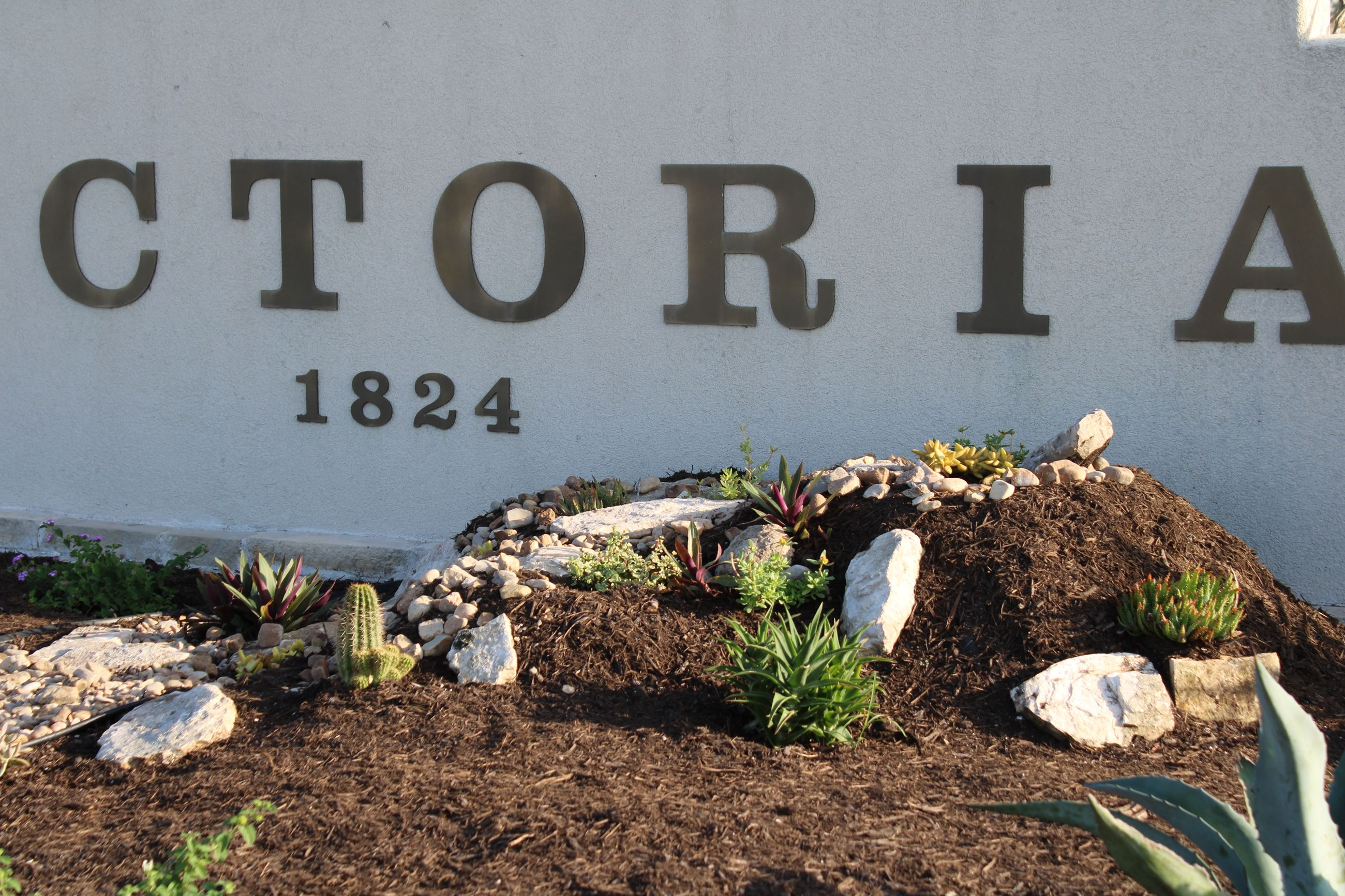Stones and cacti in front of Welcome to Victoria sign