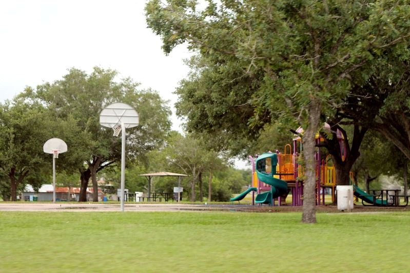 A small park with a basketball court, a children's playground and a pavilion.