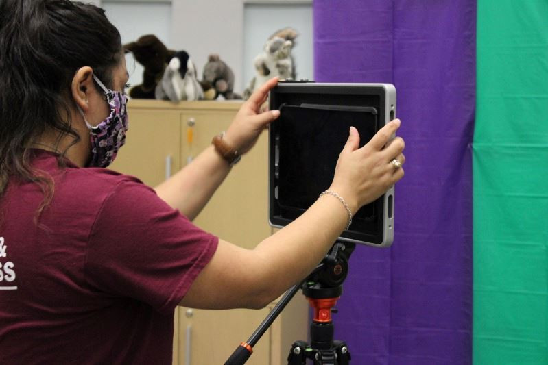 A woman sets up an iPad on a tripod to film a colorful fabric backdrop.