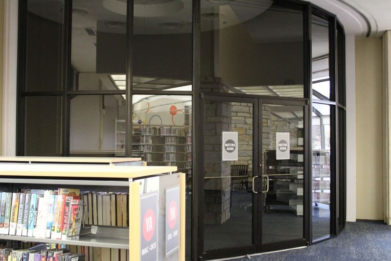 A glass-walled room in the corner of the library. The lights are off in the room.