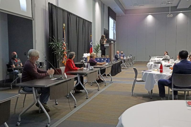 Five people sit at spaced-apart tables at the front of a ballroom. A woman stands at a podium.